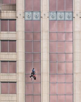 건물 창문을 청소하는 안전 로프에서 매달려 남자