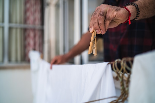 Man hanging on his clothes at home using clothespins