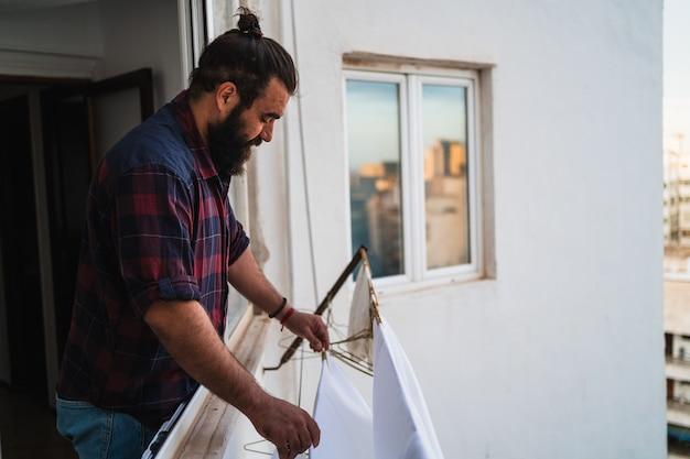Clothespins를 사용하여 집에서 그의 옷에 매달려 남자