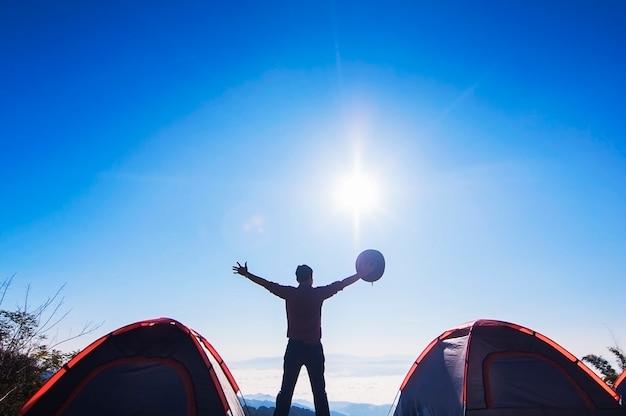 男幸せなキャンプスタンドし、朝の山の上に彼の帽子をかざして彼の手を上げる