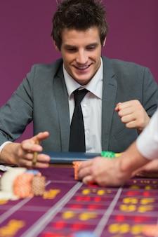 ルーレットテーブルで彼の賞金に満足している男