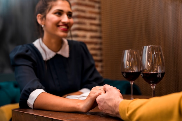 Man and happy woman holding hands at table with glasses of wine in restaurant