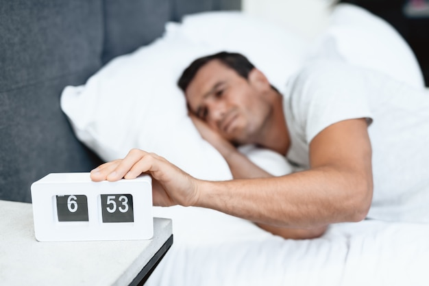 Man hardly awakes and pulls alarm off in morning