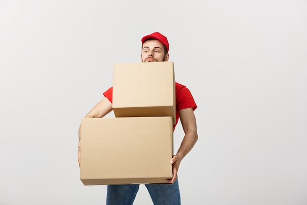 Man hardly carries the cardboard boxes, isolated on white background.