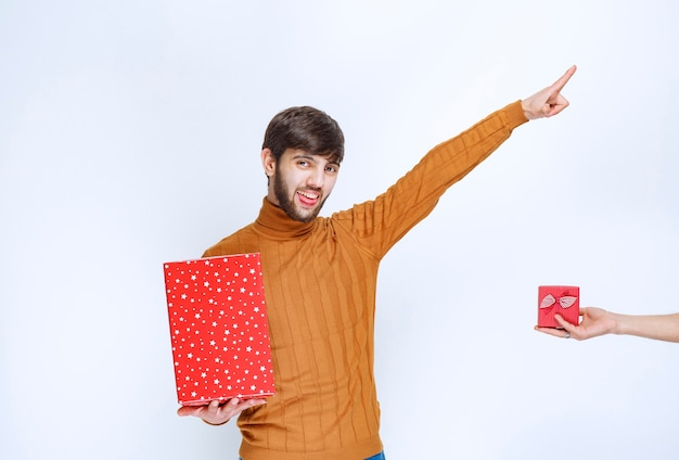 남자는 큰 빨간색 선물 상자를 가지고 있고 작은 선물 상자도 제공 받고 있습니다.