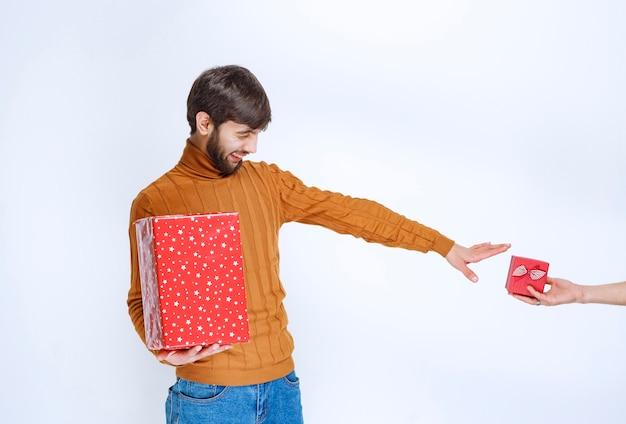 男は大きな赤いギフトボックスと別の小さなものを取るために憧れの手を持っています。
