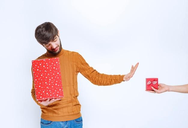 男は赤いギフトボックスを持っていて、別のものを取ることを拒否しています。