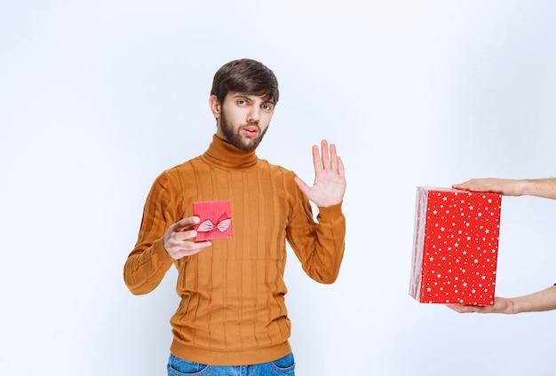 Мужчина держит красную подарочную коробку и отказывается брать другую.