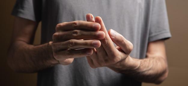 남자는 회색 배경에 아픈 손가락을 가지고 있다