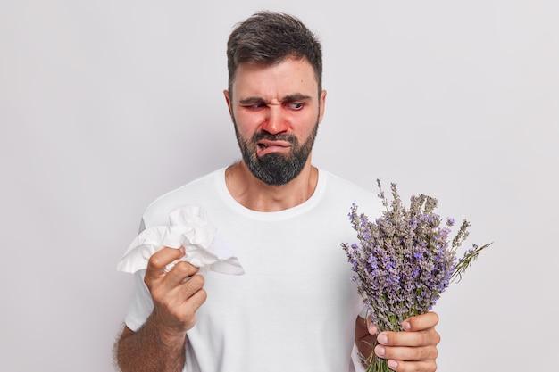男性はラベンダーにアレルギー反応があり、ティッシュを持って鼻を拭きます赤い目は白で隔離されたカジュアルなtシャツを着ています