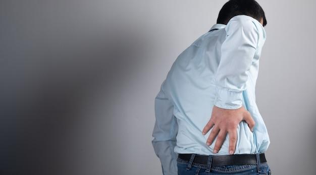 A man has a backache on a gray surface