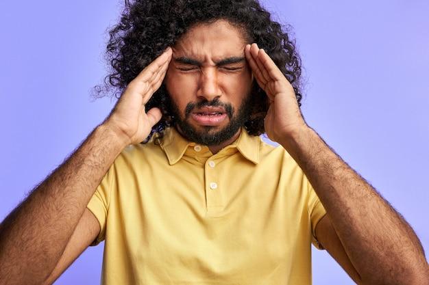 남자는 두통이 고립되어 있고, 손으로 머리를 잡고, 사원에 통증이 있으며, 눈이 보라색 벽 위에 고립 된 상태로 서 있습니다.