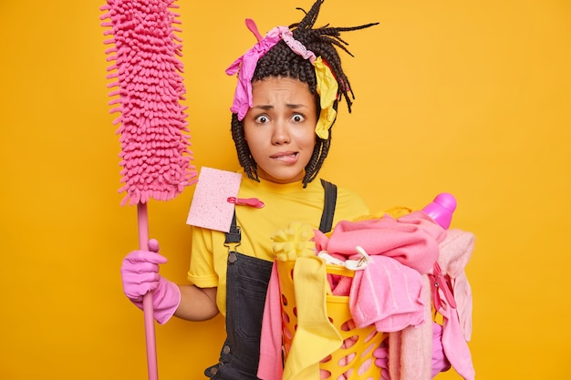 Man has nervous expression bites lips holds mop and laundry basket with dirty iems dressed in casual onalls poses on yellow