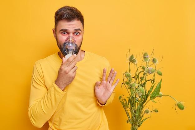 男性は肺に問題があり、喘息アレルギー症状に苦しんでいます赤い腫れ目はアレルゲンから離れています花粉にアレルギーがあります黄色の壁に隔離された吸入マスクを着用しています