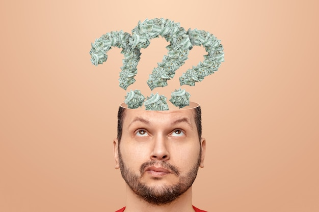 The man has question marks in his head made of banknotes, american dollars. the concept of financial crisis, bankruptcy, savings, fright, credit, debt, search for earnings.