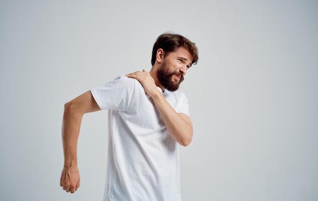 남자는 어깨 통증과 흰색 티셔츠 탈구 건강 문제가 있습니다. 고품질 사진