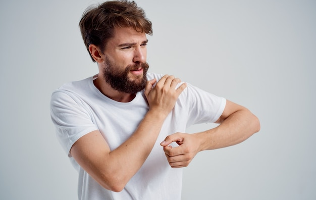 У мужчины боли в плече и проблемы со здоровьем вывих белой футболки