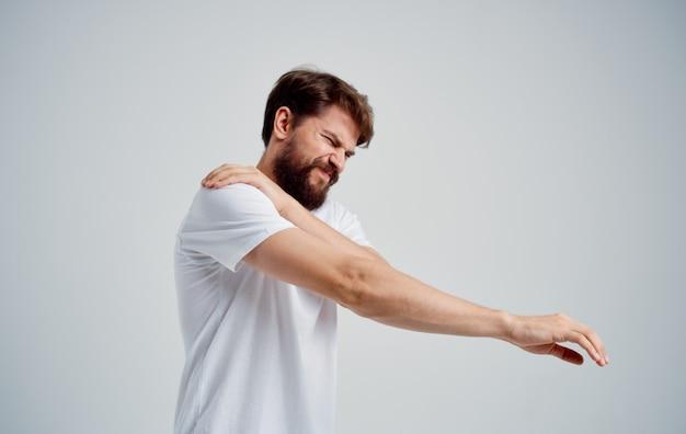 남자는 어깨 통증과 흰색 티셔츠 탈구가 있습니다.