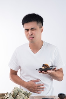 A man has a stomachache after eating delicious zongzi(rice dumpling) on dragon boat festival, asian traditional food, white background
