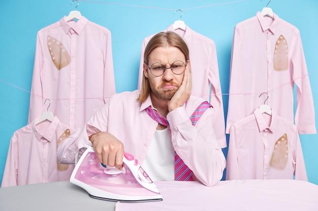 L'uomo ha un'espressione del viso imbronciata non vuole fare i lavori di casa occupato a stirare i vestiti si sente annoiato passa il fine settimana a casa facendo le faccende domestiche si appoggia a tavola si sente infelice