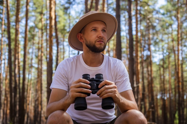 Man in a hat holds binoculars during a camping trip. hike in the mountains, forest.