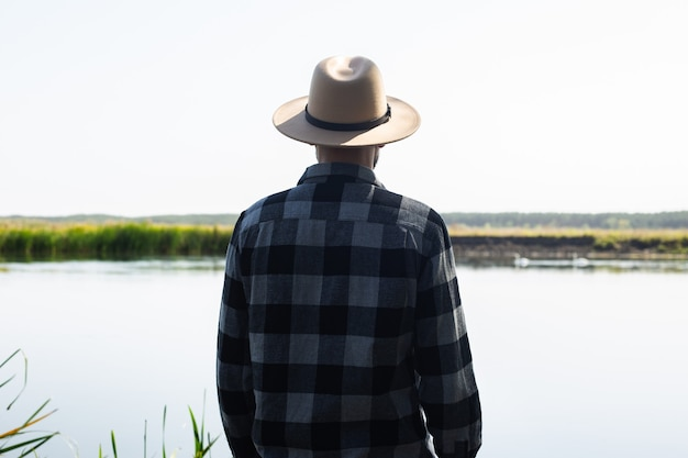 Man in a hat and a plaid shirt admires the landscape by the river.