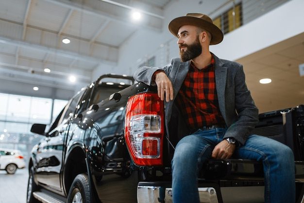 Man in hat poses at new pickup truck in car dealership. customer in vehicle showroom, male person buying transport, auto dealer business