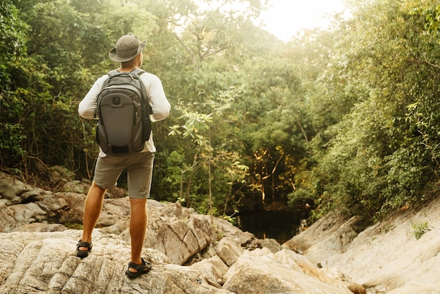 A man in a hat and shorts with a backpack is standing on a mountain looking into the distance in summer. travel and romance.