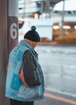Uomo con un cappello in piedi con le mani in tasca