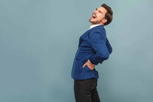 У мужчины болит спина. камни или органы почек. портрет красивого бородатого бизнесмена в синем костюме и белой рубашке. крытый студийный снимок, изолированные на светло-синем фоне