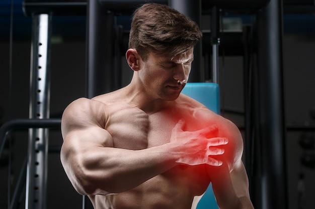 男性はジムで肩に怪我をしています。トレーニング後の痛み。ヘルスケアと医療の概念