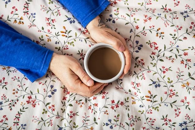 ベッドにコーヒーを持っている男