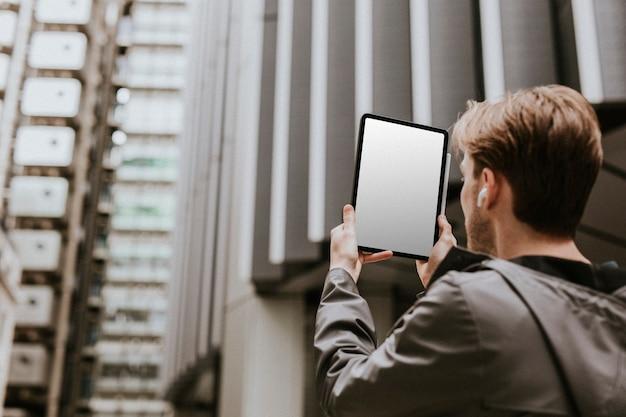 街でデジタルタブレットでビデオ通話をしている男性