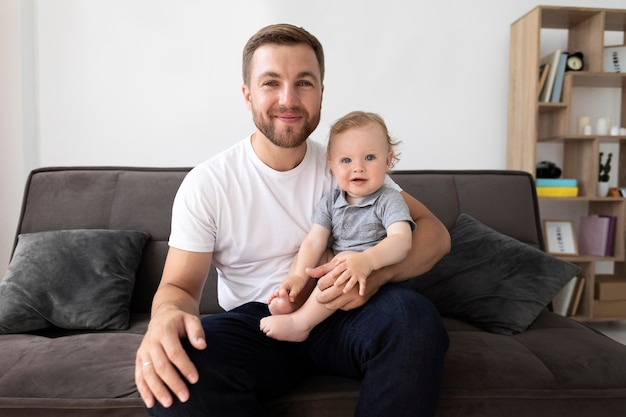 Мужчина разговаривает по видеосвязи со своей семьей, держа ребенка на руках
