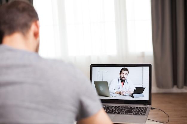 自己隔離中に医師とビデオ会議をしている男性。