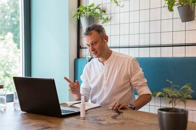 ノートパソコンで仕事のためのビデオ通話をしている男