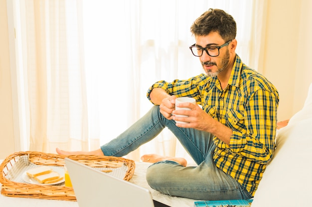 Man having breakfast on bed looking at laptop in the bedroom