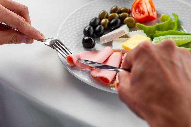 Uomo che mangia prima colazione che mangia salsiccia. veduta dall'alto.