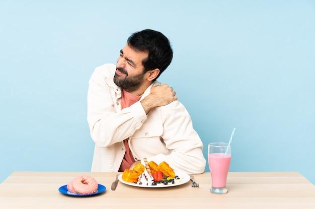 パステルカラーの壁で朝食をとっている男