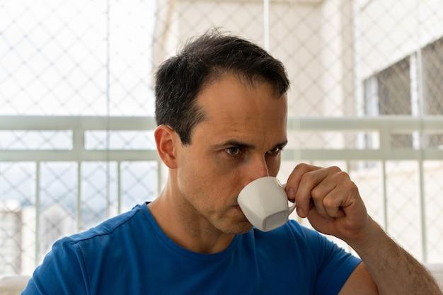 Мужчина пьет кофе и смотрит