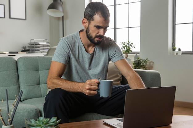 Человек пьет кофе и работает дома на ноутбуке