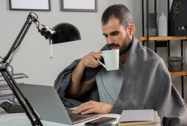 Мужчина пьет кофе во время работы из дома