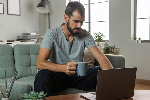 Man having coffee and working from home on laptop