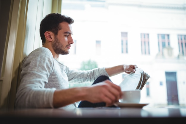 Man having a cup of coffee while reading newspaper