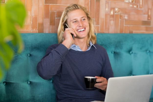 전화 통화하는 동안 커피 한잔하는 남자