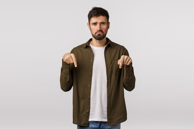 Человек, имеющий неутешительные плохие новости. расстроенный и несчастный, несчастный молодой бородатый мужчина, чувствуя сожаление или ревность, тянет грустную гримасу, хмурится, указывает вниз, жалуется