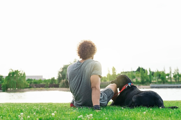 Человек веселится и играет со своей собакой в парке.