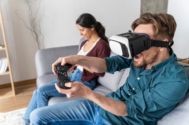 Man having fun at home on the couch with virtual reality headset playing video games