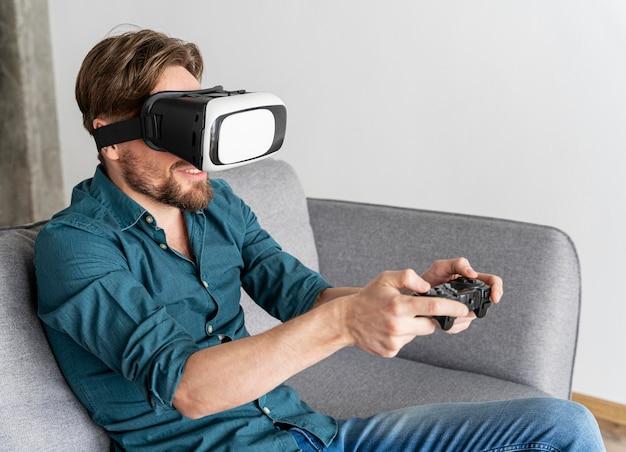 Uomo che si diverte a casa sul divano con le cuffie da realtà virtuale giocando ai videogiochi