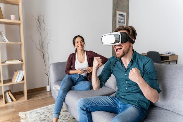 Uomo che si diverte a casa sul divano con le cuffie da realtà virtuale